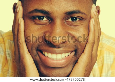 Smiling black man with hand on face