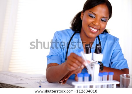 Smiling black nurse working with a test tube in blue uniform at laboratory - copyspace - stock photo