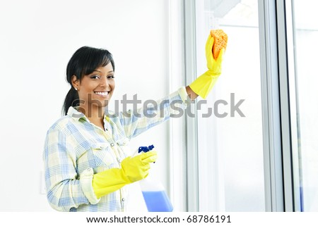 Smiling black woman cleaning windows with glass cleaner - stock photo