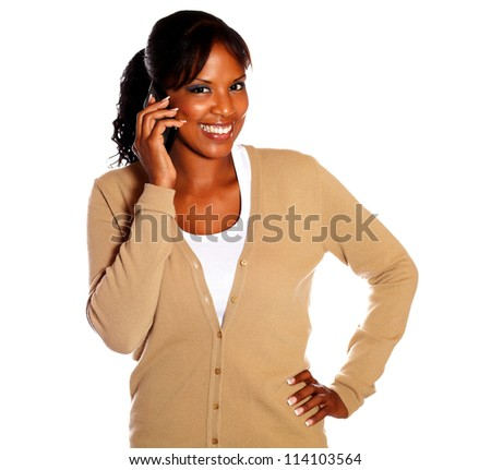 Smiling black woman looking at you while talking on cellphone against white background