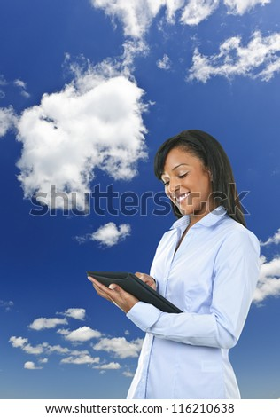 Smiling black woman with tablet computer over clouds and blue sky - stock photo