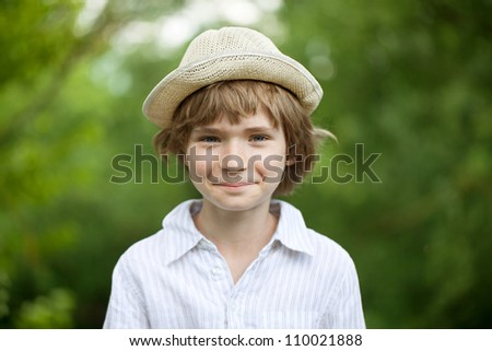 Smiling blond boy in a hat outdoors - stock photo