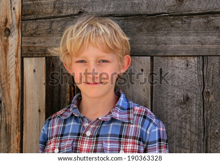 Smiling blond boy with a barn wood background. - stock photo