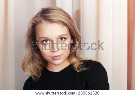 Smiling blond Caucasian girl in black, close up studio portrait - stock photo