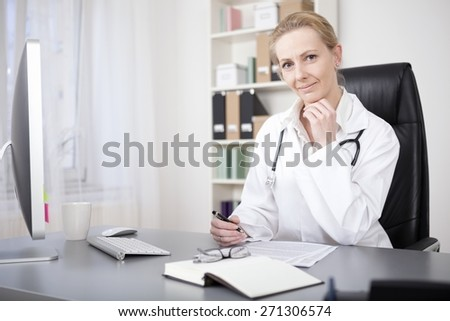 Smiling Blond Female Doctor Sitting at her Table, with Pen and Paper to Make Diagnosis, and Looking at the Camera with Hand on her Chin. - stock photo
