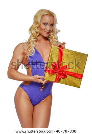 Smiling blond female in a swimwear holds gift box. - stock photo