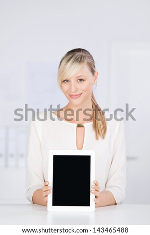 Smiling blond female shows digital tablet against the white background