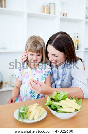 Smiling blond girl eating vegetables with her mother in the kitchen