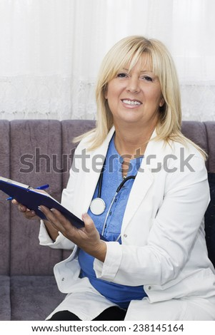 Smiling  blond haired mature nurse sitting on the sofa holding a Clipboard and looking at camera. - stock photo