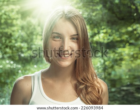 Smiling blond haired women backlit over nature green backgroun - stock photo