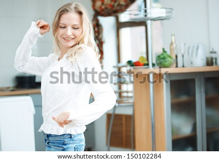 Smiling blond lady dancing at the kitchen