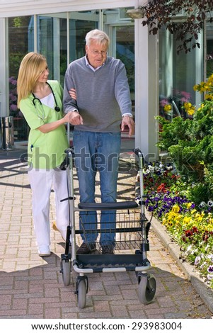 Smiling Blond Nurse Helping Senior Man to Walk with Walker, Steadying Man with Walker Outdoors in front of Building with Flower Gardens. - stock photo