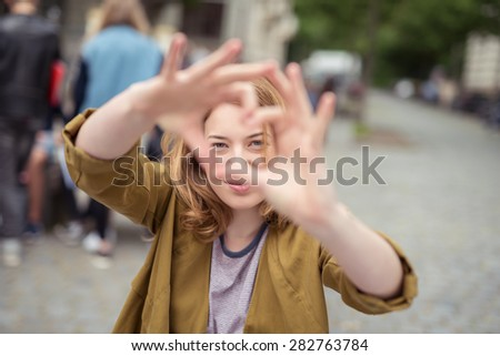Smiling blond teen girl at the street, looking at the camera through heart shaped bare hands - stock photo