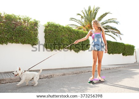 Smiling blond teenager girl skating with her pet dog in a suburban street on a sunny day, outdoors activities. People and animals recreation fitness lifestyle. Sporty living, home exterior. - stock photo