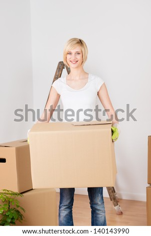 smiling blond woman carrying cardboard boxes at home - stock photo