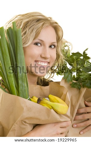 Smiling blond woman carrying fruits and vegetables - stock photo