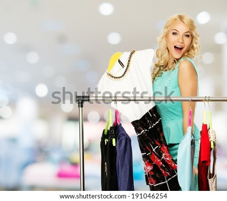 ... woman choosing clothes on a rack in a shopping mall - stock photo