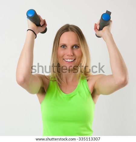 Smiling blond woman doing exercises with dumbbells isolated on white