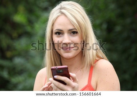 Smiling blond woman in a summer top standing in a green garden with a mobile phone in her hands looking at the camera - stock photo
