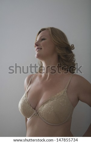 Smiling blond woman in bra against gray background - stock photo