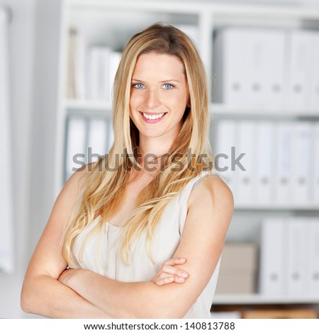 smiling blond woman in the office with folded arms - stock photo