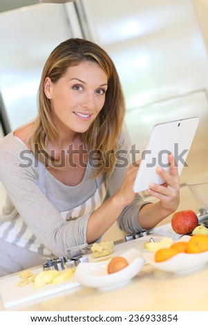 Smiling blond woman looking at recipe on digital tablet - stock photo