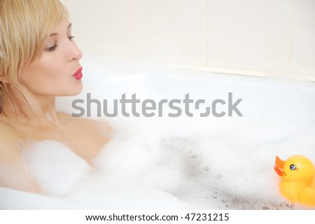 Smiling blond woman lying in bubble bath with toy duck