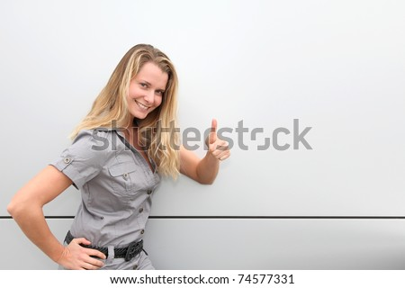 Smiling blond woman on grey background - stock photo