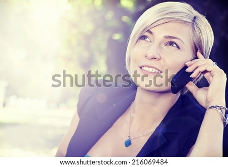 Smiling blond woman on the call outdoors, using cell phone looking up. - stock photo