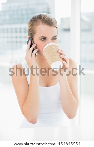 Smiling blond woman on the phone in bright room drinking coffee - stock photo