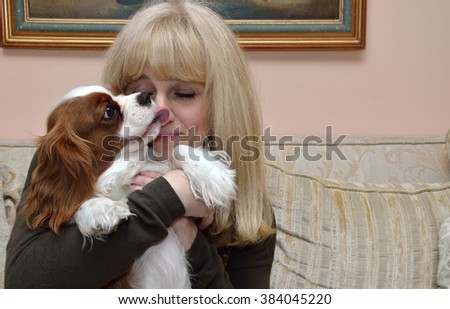 Smiling blond woman relaxing, cuddling and kissing her dog, Cavalier King Charles Spaniel (Blenheim) - stock photo