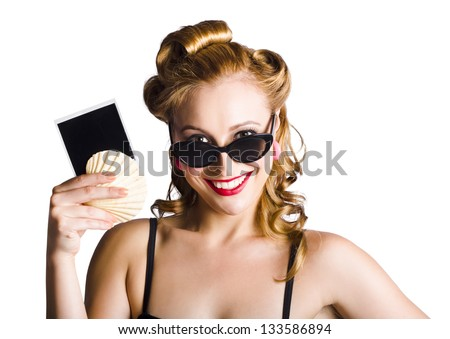 Smiling blond woman wearing sunglasses holding sea shell and empty travel photo in her left hand on white background - stock photo