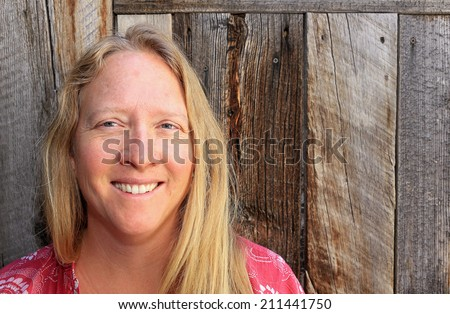Smiling blond woman with a rustic wooden background. - stock photo