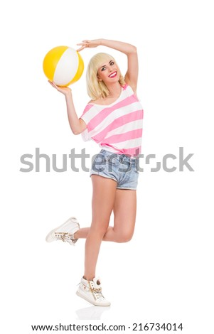 Smiling blond young woman standing on one leg and holding a beach ball above her head. Full length studio shot isolated on white. - stock photo