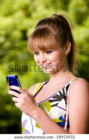 Smiling blond young woman with mobile phone outdoors