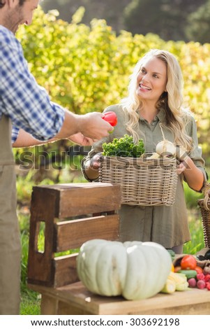 Smiling blonde customer buying vegetables in a local market