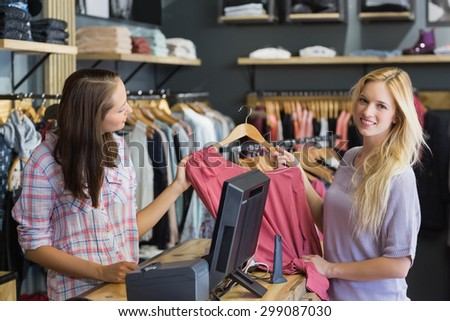 Smiling blonde doing shopping and looking at camera in clothes store - stock photo