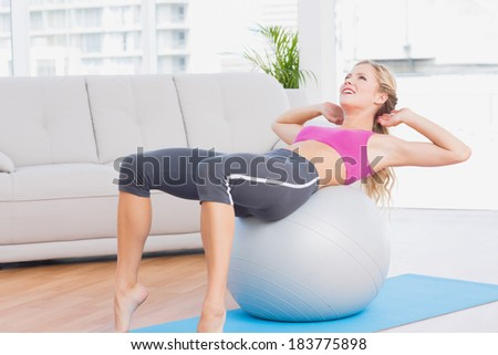 Smiling blonde doing sit ups with exercise ball at home in the living room