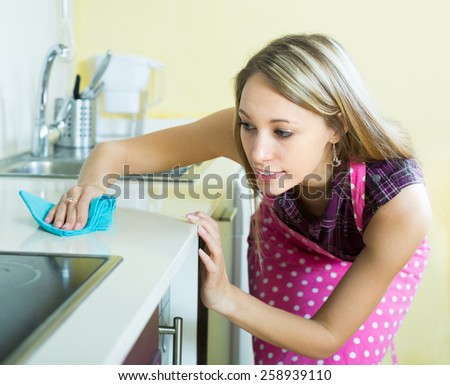 Smiling blonde girl in apron cleaning furniture in kitchen   - stock photo