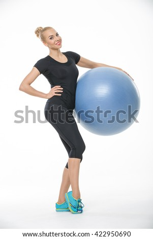 Smiling blonde girl in the sportswear stands partially sideways with a blue fitball on the white background in the studio. She wears cyan-yellow sneakers, black pants and black t-shirt. She presses - stock photo