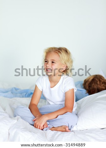 Smiling blonde girl sitting on a big bed