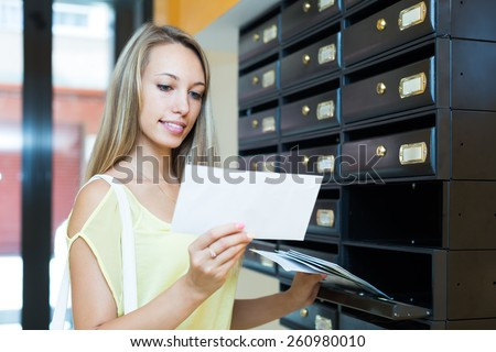 Smiling blonde girl taking junk mail out the posting box - stock photo