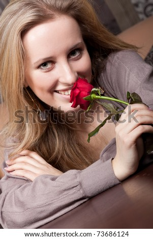 Smiling blonde girl with a red rose - stock photo