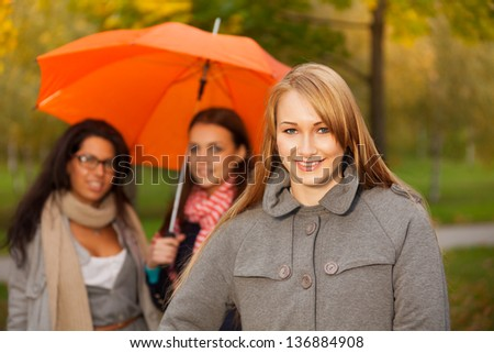 smiling blonde girl with her friends on walk in autumn park - stock photo