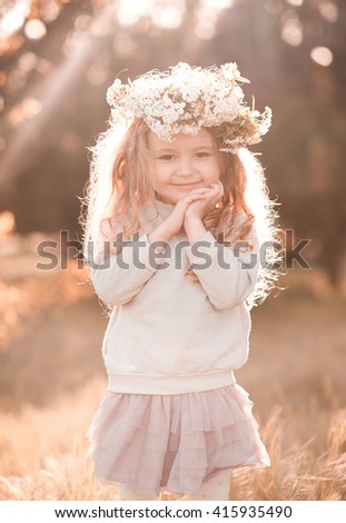 Smiling blonde girl 4-5 year old wearing floral wreath outdoors. Looking at camera. Cheerful. - stock photo