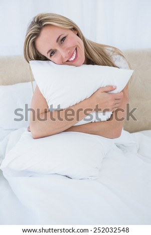 Smiling blonde holding cushion in bed at home in the bedroom