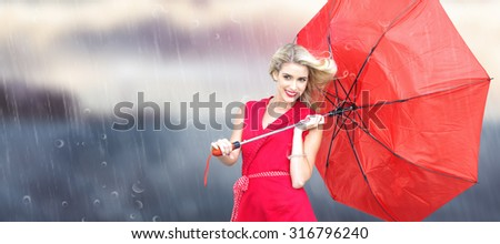 Smiling blonde holding umbrella against calm sea with lighthouse - stock photo