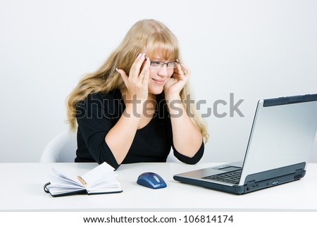Smiling blonde looks at the monitor laptop - stock photo