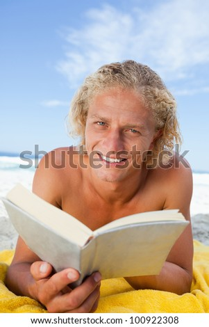Smiling blonde man reading a book while lying on his yellow beach towel - stock photo