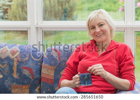 Smiling blonde middle-aged woman is relaxing on a sofa and is looking to the camera. She is holding a blue cup.